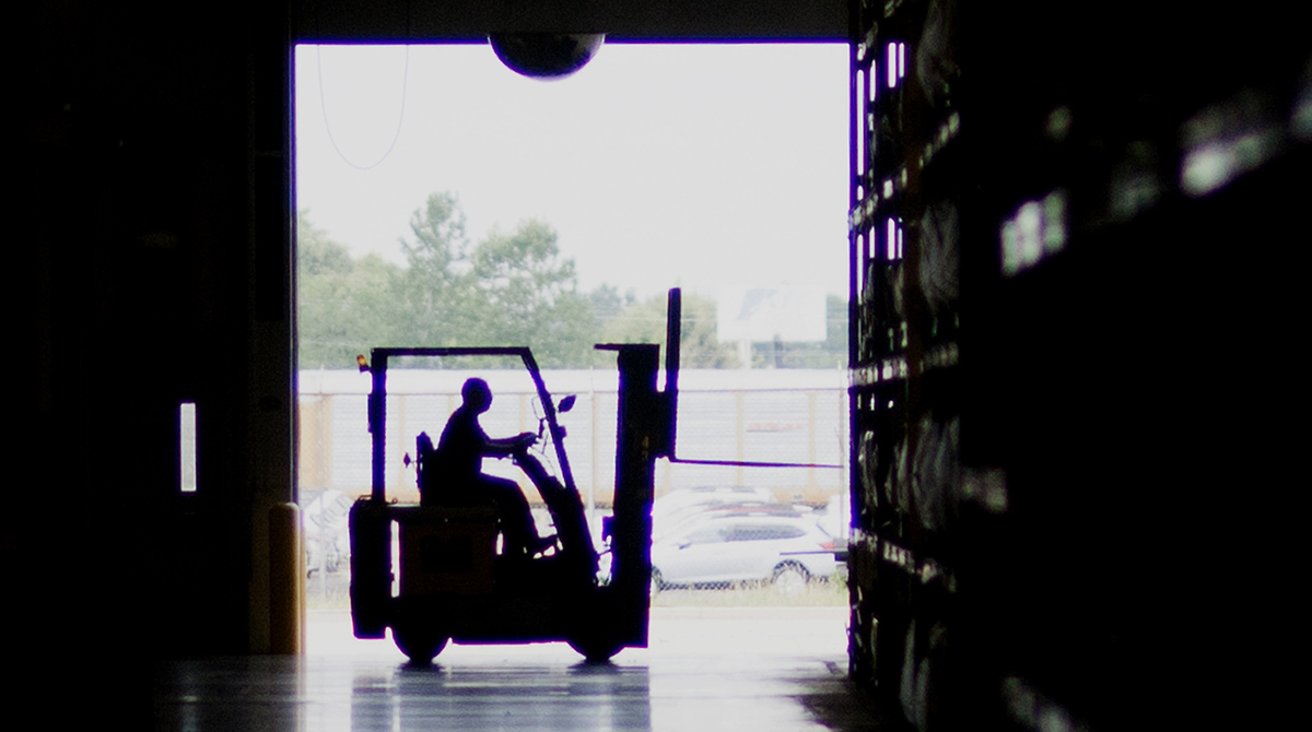 The silhouette of an employee is seen operating a forklift at the Subaru of Indiana Automotive Inc. assembly plant in Lafayette, Ind.