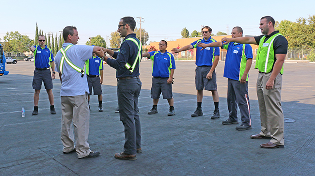 Worklete staff instruct workers on how to use their arms and elbows on the job properly.